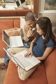 Young Hispanic couple sitting on sofa with laptops — Stock Photo