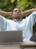 человек, расслабляющий с закрытыми глазами и руки за голову — Стоковое фото