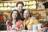 Multi-ethnic women eating in mall — Stock Photo