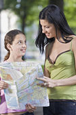 Mother and daughter consulting a map — 图库照片