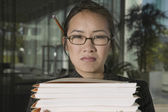 Close up portrait of frustrated businesswoman with stacks of files — Stock Photo