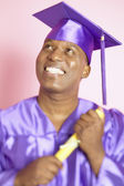 Man in cap and gown holding diploma — Stock Photo