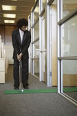 Businessman playing golf in office — Stock Photo