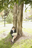 Businesswoman using laptop under tree — Stock Photo