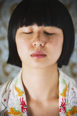 Asian girl with hair clippings on face — Stock Photo