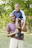 Young boy sitting on father's shoulder — Stock Photo