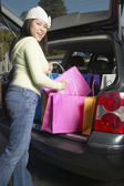Pacific Islander woman putting shopping bags into car — Stock Photo