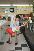 Couple dancing with soap in laundromat — Stock Photo
