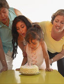 Young girl blowing out candles on her birthday cake — Stock Photo