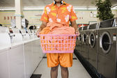 Mid section of man standing in laundromat with laundry — Stock Photo
