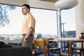 Man at home standing near window — Stock Photo