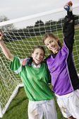 Two friends cheering in front of soccer net — Stock Photo