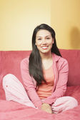Portrait of woman sitting on couch — Stock Photo