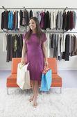Mladá žena odnosné tašky z oblečení ukládat — Stock fotografie