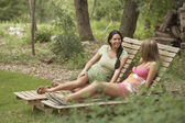 Two young women sitting on lounge chairs — Стоковое фото