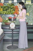 Woman weighing peppers in grocery store — Stock Photo
