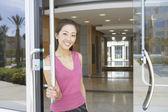 Portrait of businesswoman opening door — Stock Photo