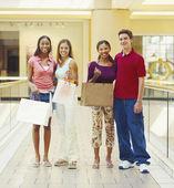 Adolescentes amigos posan en el pasillo del centro comercial — Foto de Stock