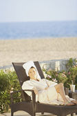 Woman in lounge chair at beach hotel — Stock Photo