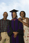 Female graduate with parents — Stock Photo
