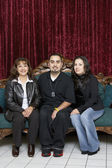 Three Hispanic family members sitting on an antique sofa — Stock Photo