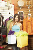 Hispanic woman holding shopping bags in boutique — Stock Photo