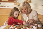 Mother and daughter decorating homemade gingerbread cookies — Stock Photo