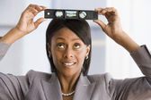 African American businesswoman holding level on head — Stock Photo