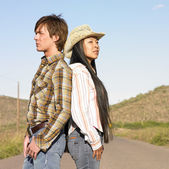 Couple standing back to back in road — Stock Photo