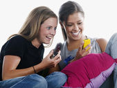 Young woman laughing with cell phones in hand — Stock Photo