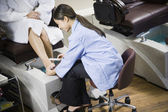 Asian nail technician filing client's toenails — Stock Photo