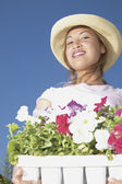 Portrait of woman carrying tray of flowers — Stock Photo