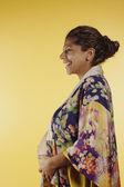 Pregnant woman wearing robe touching abdomen — Стоковое фото