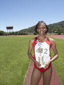 Winning female track athlete holding trophy — Stock Photo