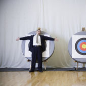 Businessman standing in front of bulls eye — Stock Photo