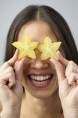 Asian woman holding star fruits over eyes — Stock Photo
