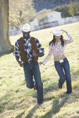 Couple in cowboy outfits walking together — Stock Photo