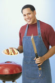 African American man barbequing hot dogs — Stock Photo