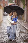 Couple walking together under umbrella — Stock Photo