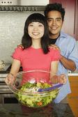 Couple with salad serving bowl — Stock Photo