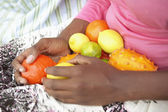 Woman's lap covered with fresh fruit — Stock Photo