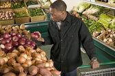 African American man choosing vegetables in supermarket — Stock Photo