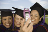 Female graduates photo messaging — Stockfoto