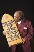 Senior African man holding hymn board — Stock Photo