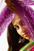 Portrait of young woman holding up a sari — Stock Photo