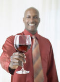 African man holding glass of red wine — Stock Photo