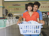 Portrait of couple with laundry hugging at laundromat — Stock Photo
