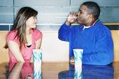 Teenage boy blowing straw at teenage girl — Stock Photo