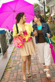 Mother and daughter walking with umbrella — Stock Photo