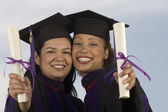 Two female graduates holding diplomas — Stock Photo
